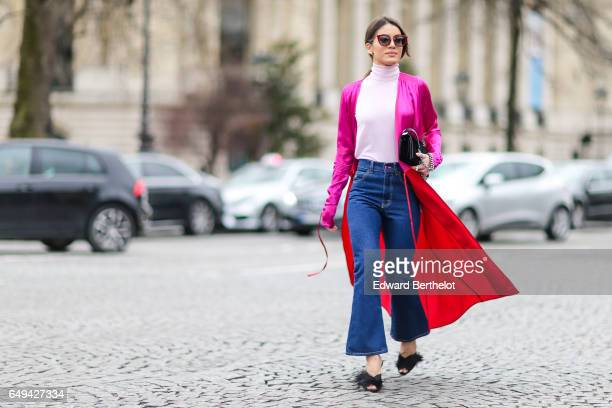 Camila Coelho wears a pink turtleneck pull over a pink and red jacket blue jeans and black shoes outside the Chanel show during Paris Fashion Week...