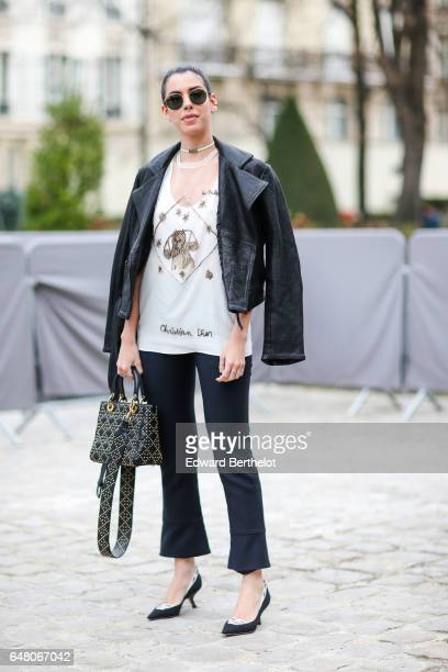 Camila Coutinho wears a black leather jacket a Dior top a Dior bag black pants black heels and attends the Christian Dior show as part of the Paris...