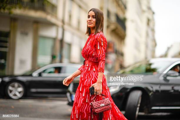 Camila Coutinho wears a red dress and a red bag outside Valentino during Paris Fashion Week Womenswear Spring/Summer 2018 on October 1 2017 in Paris...