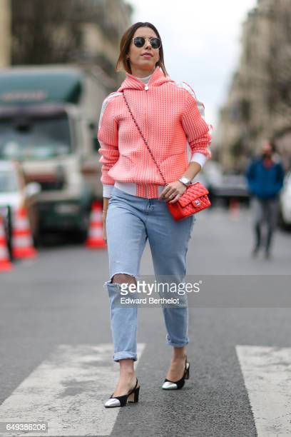 Camila Coutinho wears an orange hoodie sweater and orange Chanel bag blue ripped jeans and Chanel shoes outside the Chanel show during Paris Fashion...