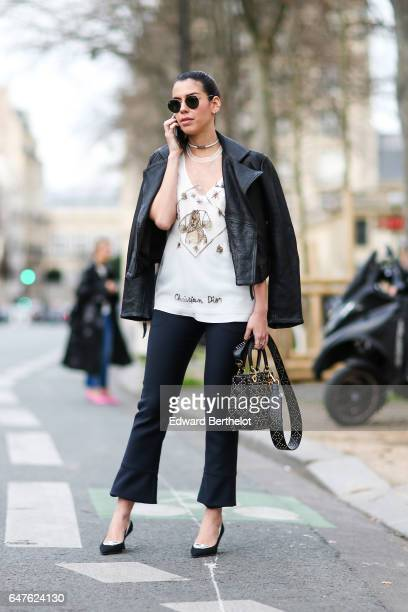 Camila Coutinho wears sunglasses an Osklen black jacket a Dior tshirt a Dior bag black pants and black heels outside the Dior show during Paris...