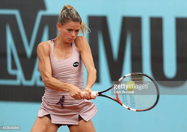 Camila Giorgi of Italy plays a backhand against Tsvetana Pironkova of Bulgaria in their first round match during day two of the Mutua Madrid Open...