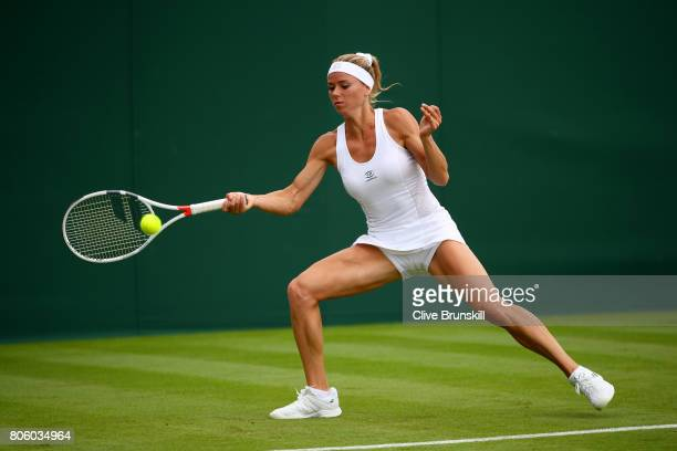 Camila Giorgi of Italy plays a forehand during the Ladies Singles first round match against Alize Cornet of France on day one of the Wimbledon Lawn...