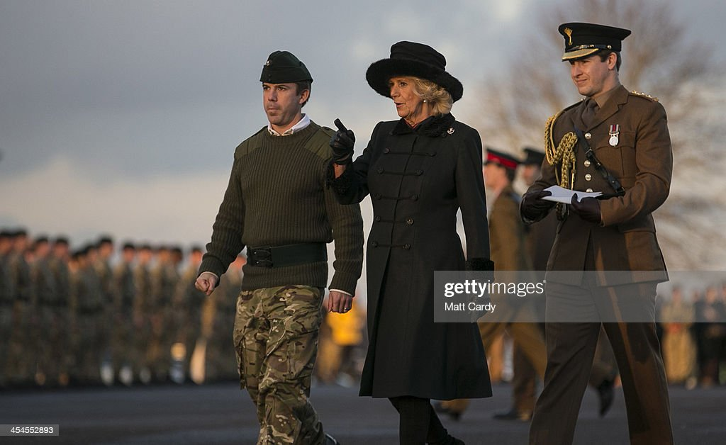 Camilla, Duchess of Cornwall (C) accompanied by CO 4 RIFLES, Lt Col Tom Bewick (L) as she arrives to present medals to soldiers from the 4th Battalion The Rifles to mark their return from Afghanistan, at their barracks in Bulford on December 9, 2013 in Wiltshire, England.
