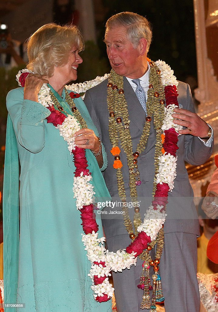 <a gi-track='captionPersonalityLinkClicked' href=/galleries/search?phrase=Camilla+-+Duchess+of+Cornwall&family=editorial&specificpeople=158157 ng-click='$event.stopPropagation()'>Camilla</a>, Duchess of Cornwall and <a gi-track='captionPersonalityLinkClicked' href=/galleries/search?phrase=Prince+Charles&family=editorial&specificpeople=160180 ng-click='$event.stopPropagation()'>Prince Charles</a>, Prince of Wales are presented with a gift as they take part in an Aarti ceremony at the Parmarth Niketan Temple on the banks of the River Ganges during day 1 of an official visit to India on November 6, 2013 in Dehradun, India. This will be the Royal couple's third official visit to India together and their most extensive yet, which will see them spending nine days in India and afterwards visiting Sri Lanka in order to attend the 2013 Commonwealth Heads of Government Meeting.
