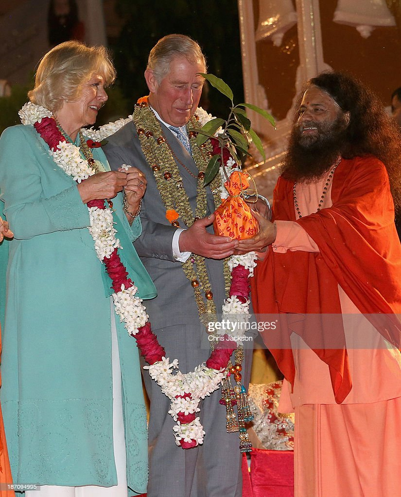 Camilla, Duchess of Cornwall and Prince Charles, Prince of Wales are presented with a gift by Pujya Swami Chidanand Saraswatiji Maharaj as they take part in an Aarti ceremony at the Parmarth Niketan Temple on the banks of the River Ganges during day 1 of an official visit to India on November 6, 2013 in Dehradun, India. This will be the Royal couple's third official visit to India together and their most extensive yet, which will see them spending nine days in India and afterwards visiting Sri Lanka in order to attend the 2013 Commonwealth Heads of Government Meeting.