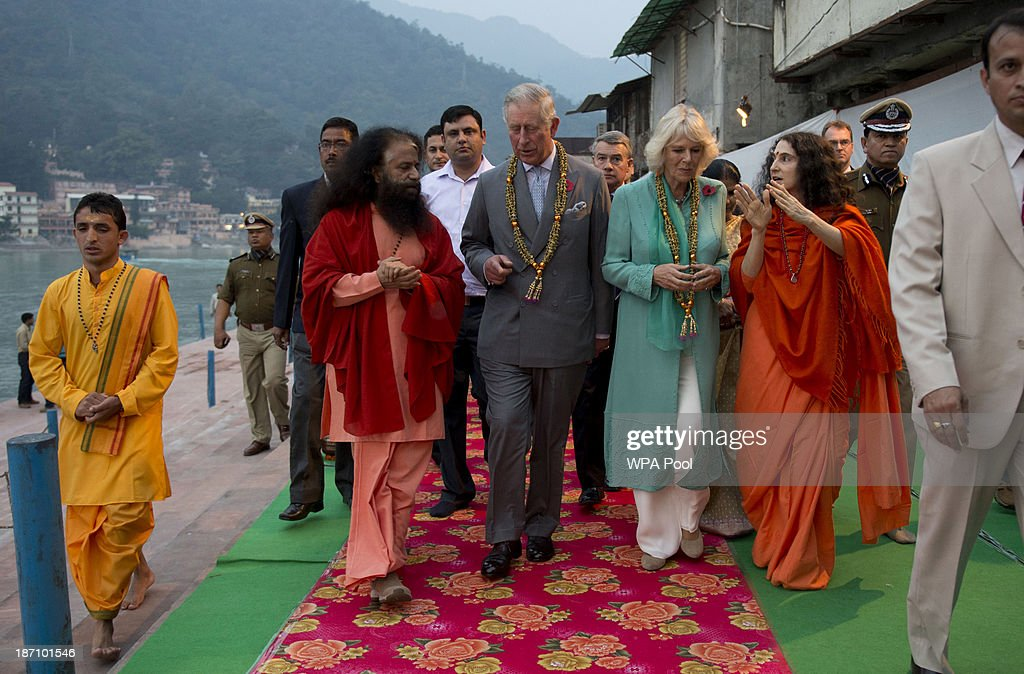 Camilla, Duchess of Cornwall and Prince Charles, Prince of Wales arrive to take part in an Aarti ceremony lead by Pujya Swami Chidanand Saraswatiji Maharaj (L) at the Parmarth Niketan Temple on the banks of the River Ganges during day 1 of an official visit to India on November 6, 2013 in Rishikesh, India. This will be the Royal couple's third official visit to India together and their most extensive yet, which will see them spending nine days in India and afterwards visiting Sri Lanka in order to attend the 2013 Commonwealth Heads of Government Meeting.