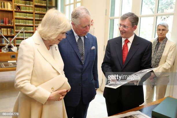 Camilla Duchess of Cornwall and Prince Charles Prince of Wales look at artworks presented by the Director of The British School Christopher Smith as...