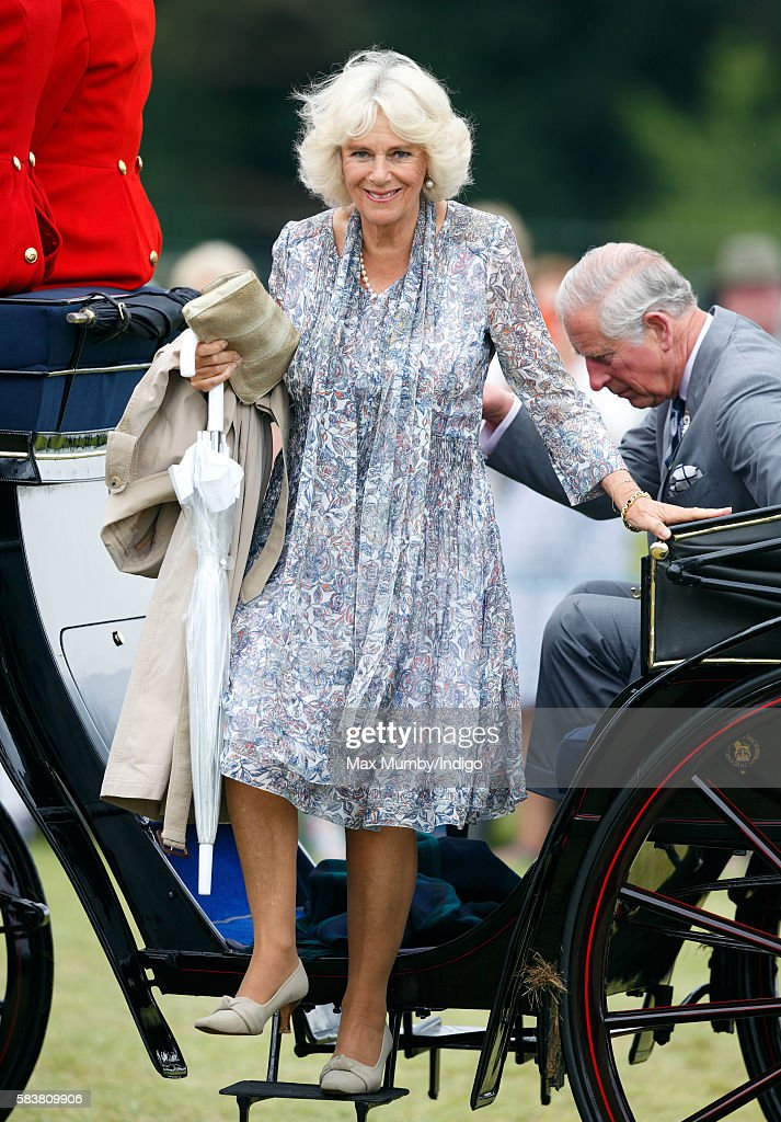Camilla Duchess of Cornwall and Prince Charles Prince of Wales step out of a horse drawn carriage as they arrive for a visit to the Sandringham...