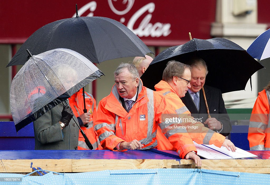 Camilla, Duchess of Cornwall (L) and Prince Charles, Prince of Wales (R) shelter under umbrellas as they view the Crossrail development site before travelling on a Metropolitan line underground train from Farringdon to King's Cross on January 30, 2013 in London, England. The Prince of Wales and The Duchess of Cornwall are marking the 150th anniversary of London Underground to emphasise the importance of engineering and infrastructure development in the UK.