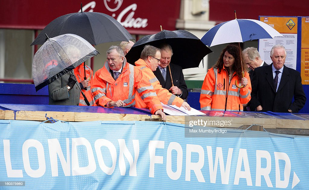 Camilla, Duchess of Cornwall (L) and Prince Charles, Prince of Wales (C) shelter under umbrellas as they view the Crossrail development site before travelling on a Metropolitan line underground train from Farringdon to King's Cross on January 30, 2013 in London, England. The Prince of Wales and The Duchess of Cornwall are marking the 150th anniversary of London Underground to emphasise the importance of engineering and infrastructure development in the UK.