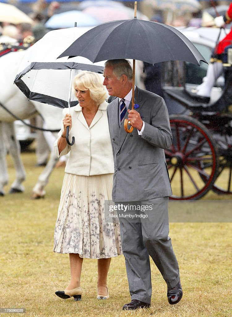 Camilla, Duchess of Cornwall and Prince Charles, Prince of Wales shelter under umbrellas as they visit the 132nd Sandringham Flower Show at Sandringham House on July 31, 2013 in King's Lynn, England.