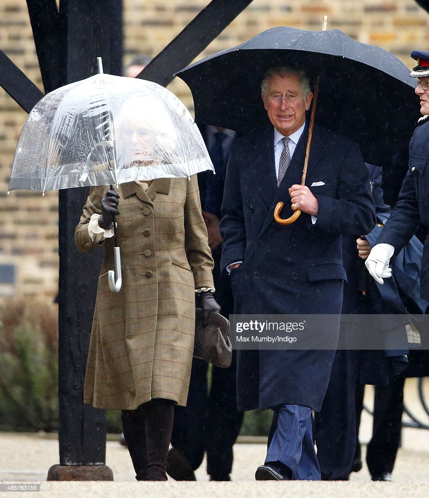 Camilla, Duchess of Cornwall and Prince Charles, Prince of Wales shelter under umbrellas as they arrive for a visit to High House Production Park, The Royal Opera House's Production Workshop on a day of engagements in Essex on January 29, 2014 in Purfleet, England.