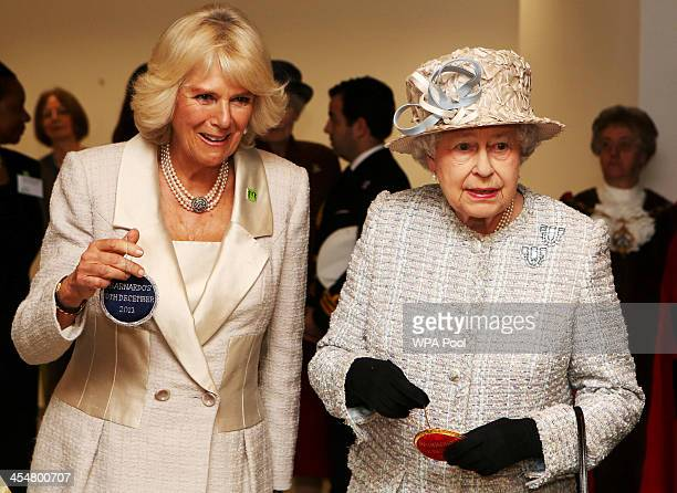 Camilla Duchess of Cornwall and Queen Elizabeth II visit the new Barnardo's HQ in Barkingside on December 10 2013 in London England