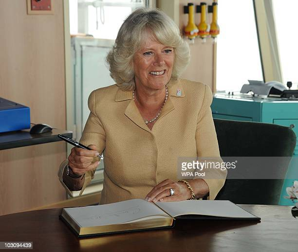 Camilla Duchess Of Cornwall asks for a new pen as she signs the guest book on board the Cunard Liner 'Queen Victoria while on her visit to Merseyside...
