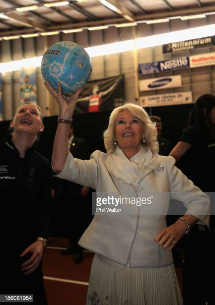 Camilla Duchess of Cornwall attempts a netball shot with Katrina Grant of the New Zealand Silver Ferns netball team at the Milennium Sports Institute...