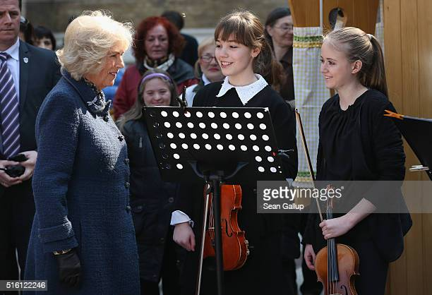 Camilla Duchess of Cornwall chats with young musicins from an orchestra performing while visiting a market square with Prince Charles Prince of Wales...