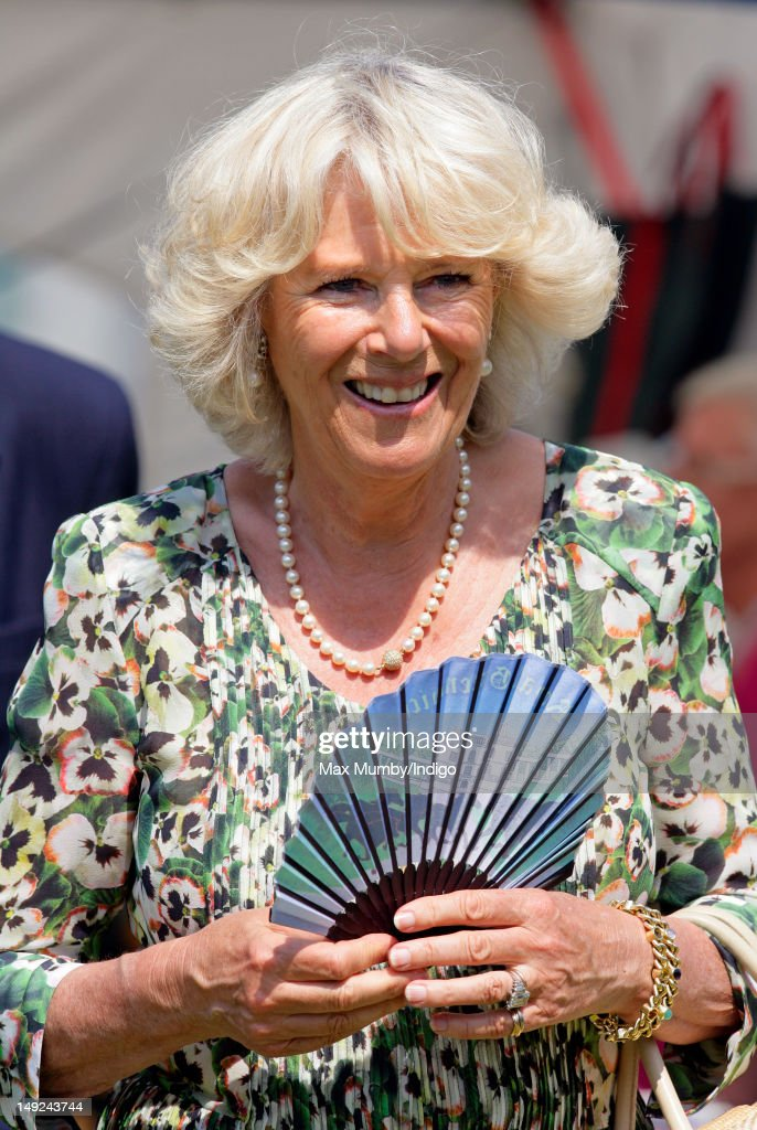 Camilla, Duchess of Cornwall cools herself with a Royal Greenwich design handheld fan as she tours the Sandringham Flower Show along with Prince Charles, Prince of Wales at Sandringham on July 25, 2012 in King's Lynn, England.