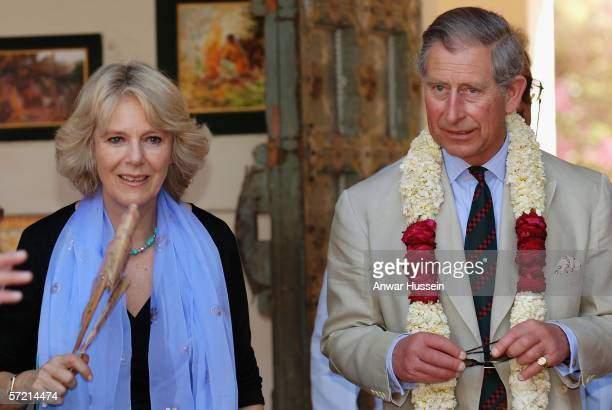 Camilla Duchess of Cornwall fans herself in the heat and Prince Charles Prince of Wales wears a garland as they visit the arts and craft market at...