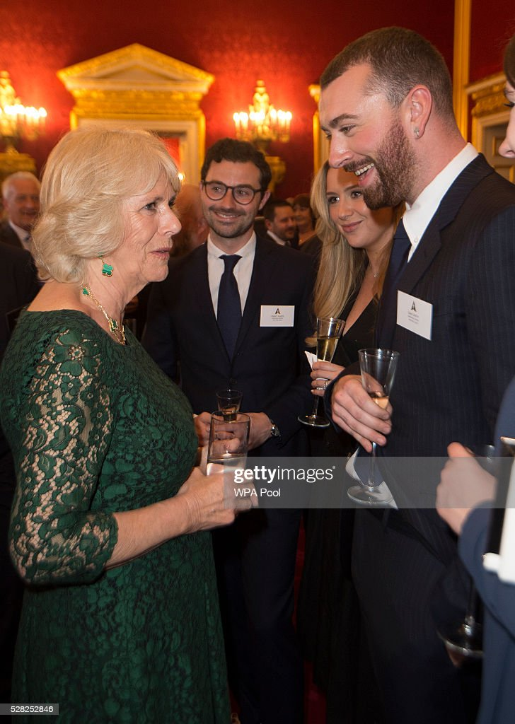 Camilla, Duchess of Cornwall greets Sam Smith during a reception at St James's Palace for British Oscar winners on May 4, 2016 in London, United Kingdom.