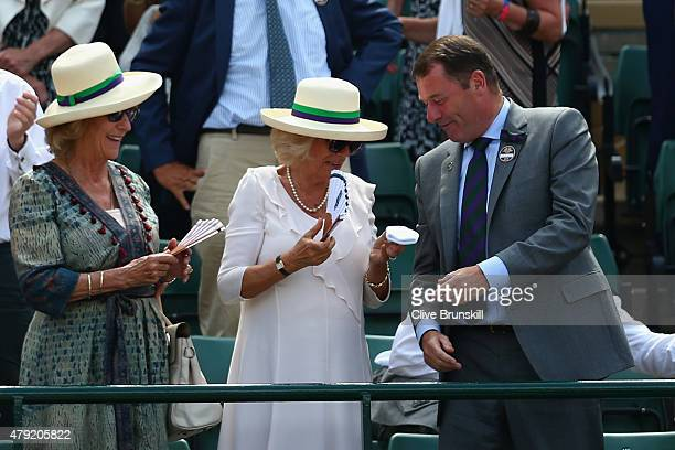 Camilla Duchess of Cornwall holds the wrist band that Andy Murray threw into the crowd with AELTC Chairman Philip Brook on Centre Court during day...