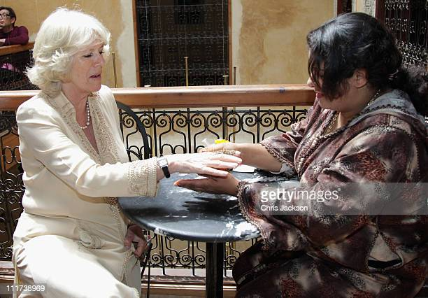 Camilla Duchess of Cornwall is given a henna tattoo as she visits Clock Cafe in the Medina on day three of a three day visit to Morocco on April 6...