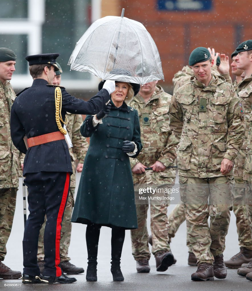 camilla-duchess-of-cornwall-is-handed-an-umbrella-by-an-equerry-as-picture-id645950672