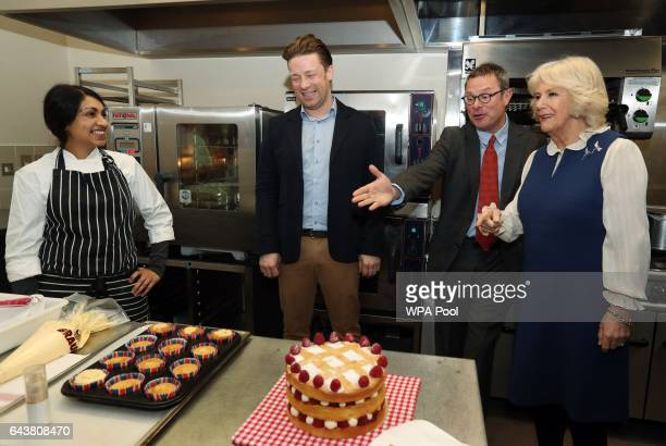 Camilla Duchess of Cornwall is shown a selection of baked goods by chef Meera Jamie Oliver and Hugh FearnleyWhittingstall in the kitchen during a...