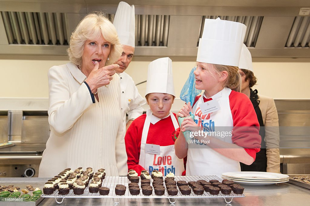Camilla, Duchess of Cornwall licks icing from her thumb as she meets Cory Hogg (C) and Katie Elder, pupils from Eastington Primary School, Gloucestershire, in the kitchens of Buckingham Palace on June 15, 21012 in London, England. Queen Elizabeth II and the Duchess of Cornwall met winners of the 'Cook for the Queen' competition, who created the menu served at a reception at Buckingham Palace.