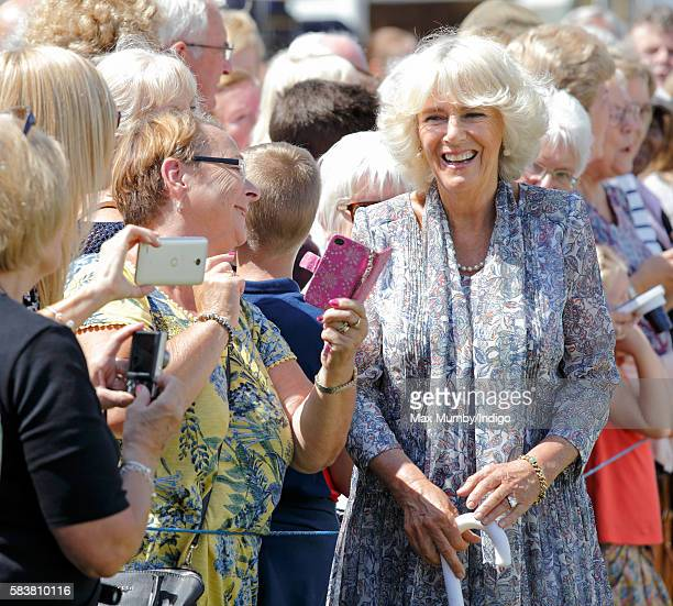 Camilla Duchess of Cornwall poses for a selfie with a member of the public as she visits the Sandringham Flower Show at Sandringham House on July 27...