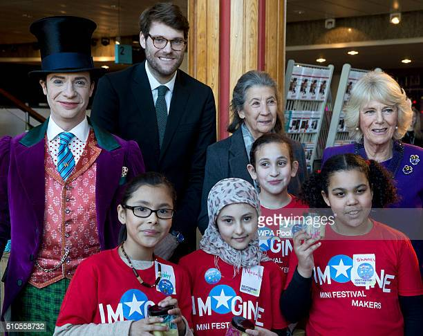 Camilla Duchess of Cornwall poses with children attending the 'Imagine' festival actor Jonothan Slinger as 'Willy Wonka' Roald Dahl's grandson Luke...