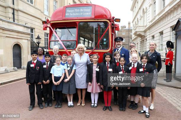 Camilla Duchess of Cornwall poses with comedian and author David Walliams dressed as an bus conductor school children from Hemlington Hall Academy in...