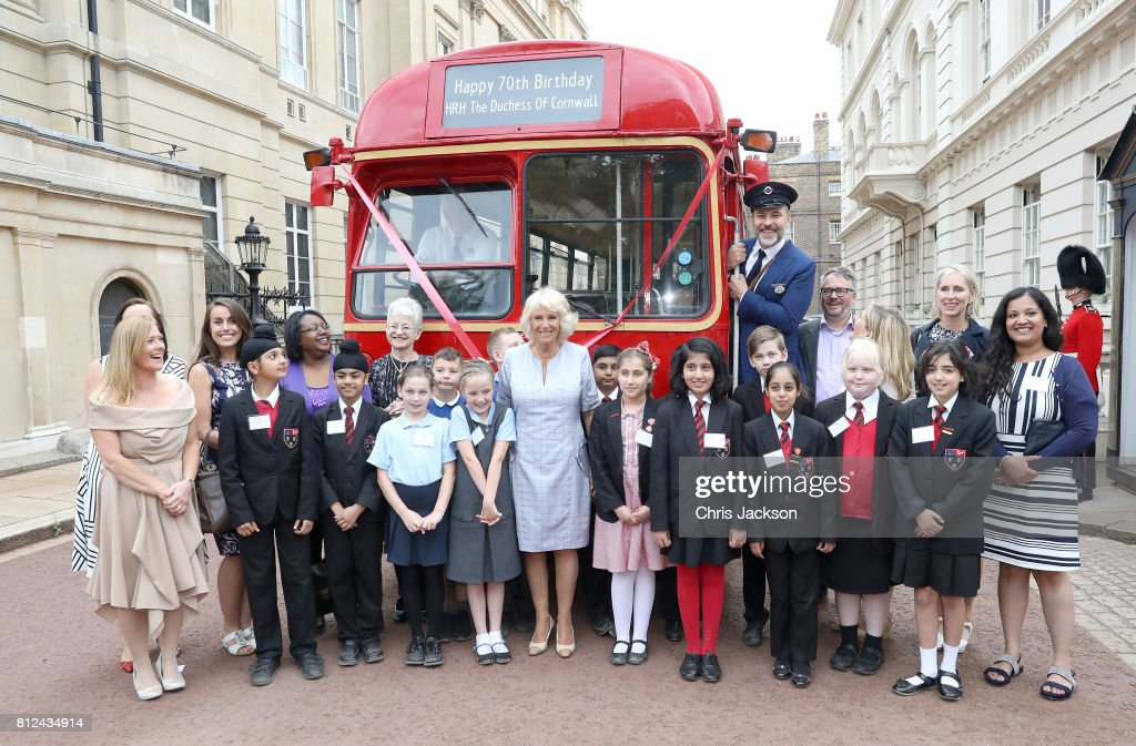 Camilla, Duchess of Cornwall (C) poses with comedian and author David Walliams, dressed as an bus conductor, school children from Hemlington Hall Academy in Middlesbrough and Berkeley Primary School in Hounslow and guests during a tea party hosted by the Duchess of Cornwall to celebrate the Duchess's Bookshelves Project at Clarence House on July 11, 2017 in London, England. The Project is an initiative to find the nation's 70 favourite children's books to mark the Duchess of Cornwall's 70th birthday.