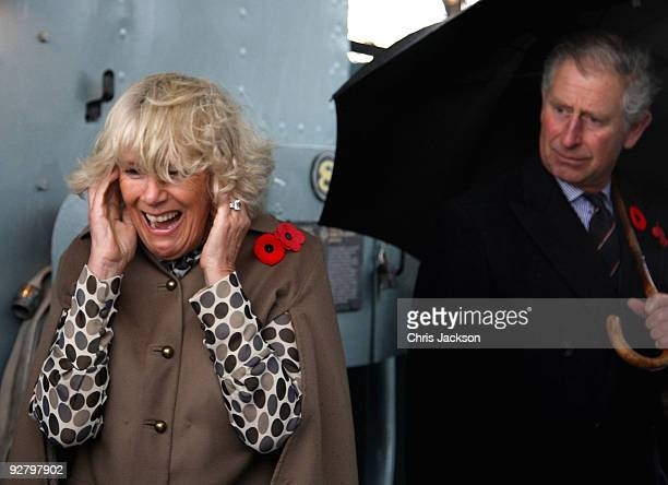 Camilla Duchess of Cornwall puts her fingers in her ears as Prince Charles Prince of Wales fires the gun on HMCS Haida on November 5 2009 in Hamilton...