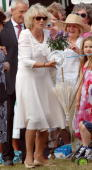 Camilla Duchess of Cornwall receives flowers from a child during a visit to Sandringham Flower show on July 30 2008 in Sandringham England