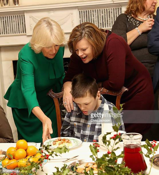Camilla Duchess of Cornwall serves sausage and mash to children from Helen and Douglas House during a reception at Clarence House on December 14 2016...