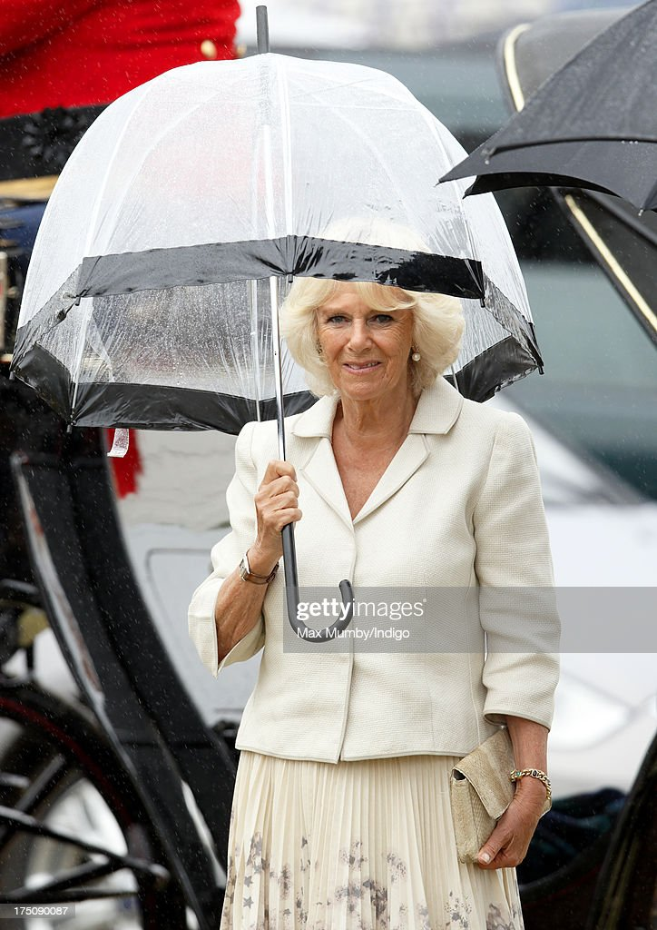 Camilla, Duchess of Cornwall shelters under an umbrella as she and Prince Charles, Prince of Wales visit the 132nd Sandringham Flower Show at Sandringham House on July 31, 2013 in King's Lynn, England.