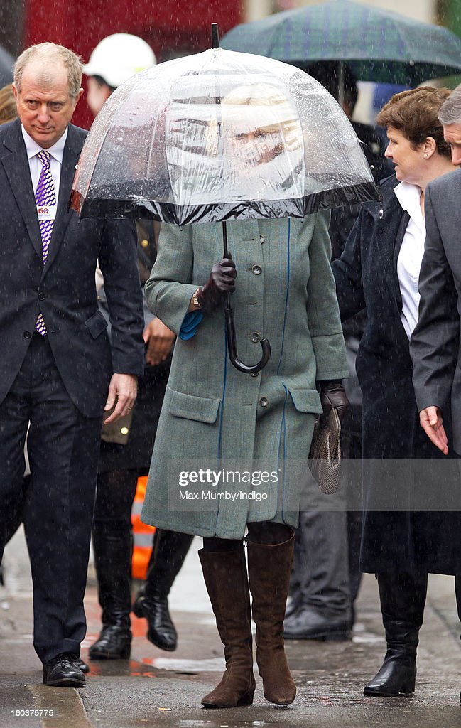 Camilla, Duchess of Cornwall shelters under an umbrella as she arrives at Farringdon Underground Station to view the nearby Crossrail development site before travelling on a Metropolitan underground train to King's Cross on January 30, 2013 in London, England. The Prince of Wales and The Duchess of Cornwall are marking the 150th anniversary of London Underground to emphasise the importance of engineering and infrastructure development in the UK.