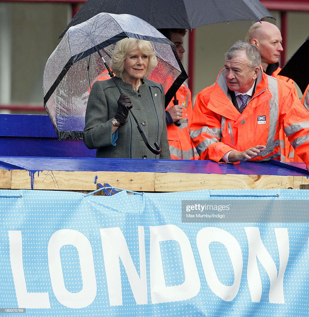 Camilla, Duchess of Cornwall shelters under an umbrella as she views the Crossrail development site before travelling on a Metropolitan underground train from Farringdon to King's Cross on January 30, 2013 in London, England. The Prince of Wales and The Duchess of Cornwall are marking the 150th anniversary of London Underground to emphasise the importance of engineering and infrastructure development in the UK.
