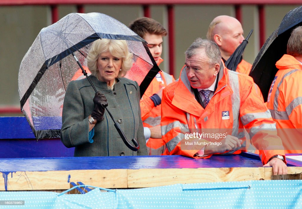 Camilla, Duchess of Cornwall shelters under an umbrella as she views the Crossrail development site before travelling on a Metropolitan line underground train from Farringdon to King's Cross on January 30, 2013 in London, England. The Prince of Wales and The Duchess of Cornwall are marking the 150th anniversary of London Underground to emphasise the importance of engineering and infrastructure development in the UK.