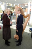 Camilla Duchess Of Cornwall speaks to a young girl near a harp as she visits St Catherine's School in Bramley Surrey on February 13 2014 in Guildford...