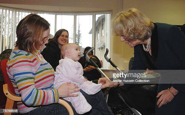 Camilla Duchess of Cornwall tickles a baby's foot as she opens the new Hathaway Medical Centre on February 12 2007 in Chippenham England