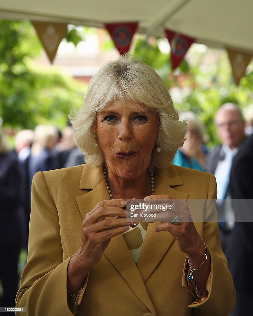 Camilla, Duchess of Cornwall tries produce during a reception to celebrate the 21st anniversary of Duchy originals products at Clarence House on September 11, 2013 in London, England. The reception was held in the gardens of Clarence House, and attended by Duchy suppliers, Waitrose and other international stockists, customers, charitable beneficiaries and representatives of some of the charities who benefit from the sale of the products.