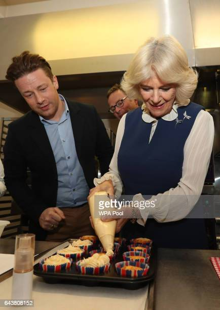 Camilla Duchess of Cornwall uses a piping bag to apply icing to cupcakes under the gaze of Jamie Oliver and Hugh FearnleyWhittingstall in the kitchen...