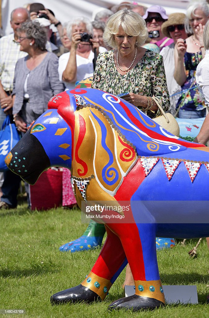 Camilla, Duchess of Cornwall views a multi coloured decorated model lion as she tours the Sandringham Flower Show along with Prince Charles, Prince of Wales at Sandringham on July 25, 2012 in King's Lynn, England.