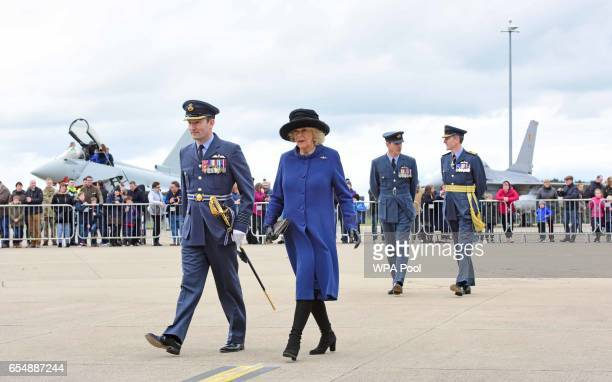 Camilla Duchess of Cornwall walks alongside Group Captain David Arthurton during a visit to RAF Leeming for the 100 Squadron Centenary on March 18...