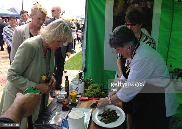 Camilla Duchess of Cornwall watches food being cooked during a farmers market walk about in on November 15 2012 in Fielding New Zealand Britain's...