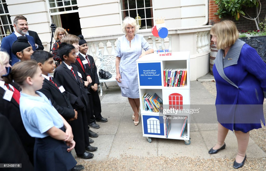Camilla, Duchess of Cornwall (C) with school children from Hemlington Hall Academy in Middlesbrough and Berkeley Primary School in Hounslow during a tea party hosted by the Duchess of Cornwall to celebrate the Duchess's Bookshelves Project at Clarence House on July 11, 2017 in London, England. The Project is an initiative to find the nation's 70 favourite children's books to mark the Duchess of Cornwall's 70th birthday.