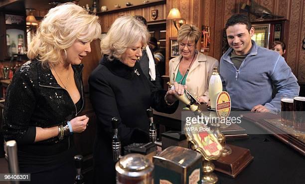 Camilla The Duchess of Cornwall pulls a pint of beer as she meets actors Beverley Callard who plays landlady Liz McDonald Anne Kirkbride who plays...