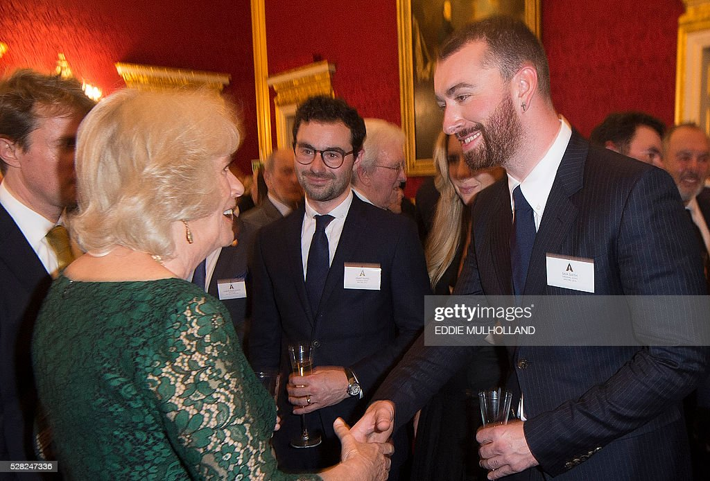 Camilla, The Duchess of Cornwall speaks to British singer Sam Smith at a reception for British Oscar winners in central London on May 4, 2016. The Oscars represent excellence in filmmaking and it is a testament to the talent in the United Kingdom that more than��300��British artists and filmmakers have earned this��honour. / AFP / POOL / Eddie Mulholland